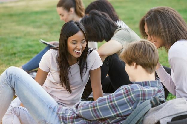 Lachende studenten buiten studeren