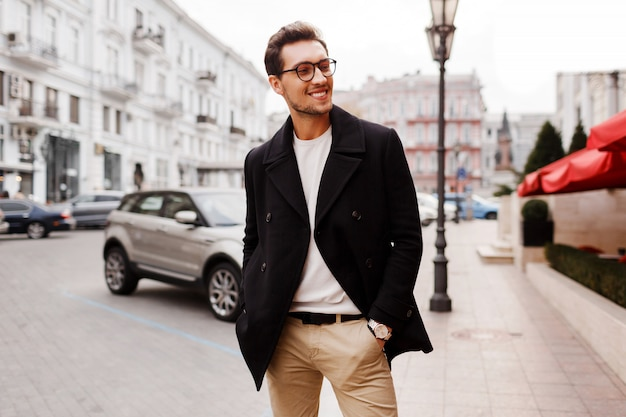 Lachende sucsessful knappe man in jas poseren op straat. mannelijke herfstmodetrends.