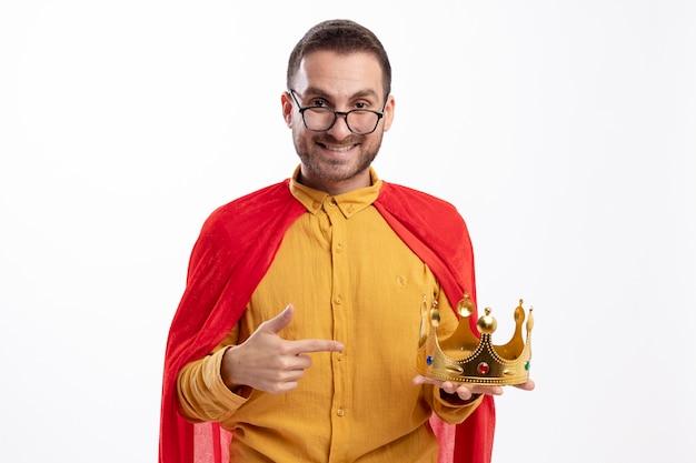 Lachende superheld man in optische bril met rode mantel houdt en wijst naar kroon geïsoleerd op een witte muur
