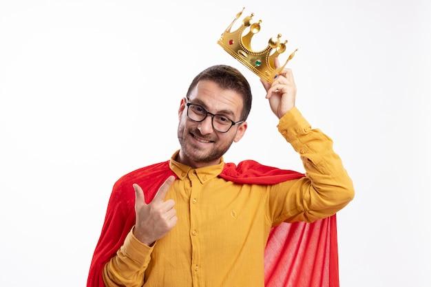 Lachende superheld man in optische bril met rode mantel houdt kroon boven het hoofd en wijst naar voorzijde geïsoleerd op een witte muur