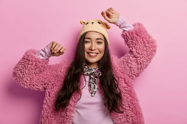 Lachende tedere jonge vrouw doet overwinningsdans, voelt zich vrolijk en vrolijk, houdt de handen omhoog, draagt hoed en bontjas, voelt de smaak van succes