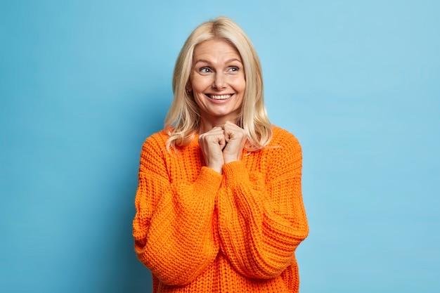 Lachende tedere vrouw van middelbare leeftijd met licht haar brede glimlach houdt de handen bij elkaar en kijkt weg heeft een dromerige uitdrukking gekleed in een oversized trui staat over de blauwe muur.