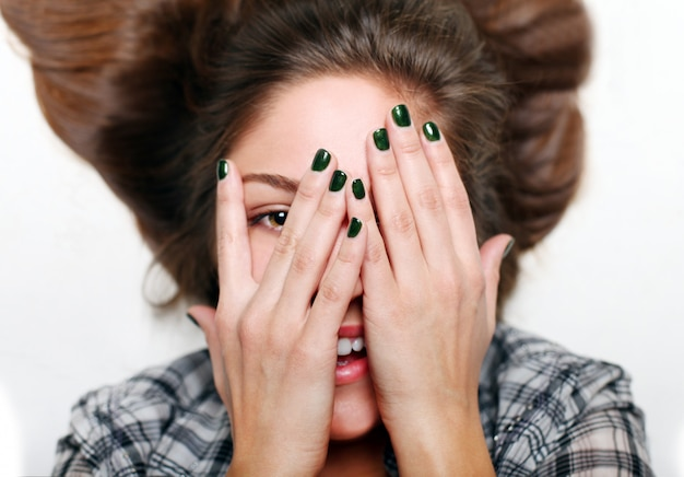 Lachende tiener handen van gezicht, groene nail art