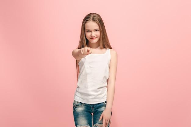 Lachende tiener meisje wijst naar camera, halve lengte close-up portret op roze studio achtergrond.