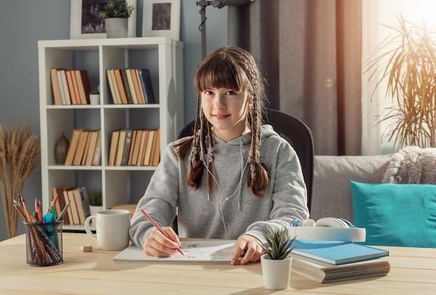 Lachende tiener meisje zit aan bureau kijken camera, studeren vanuit huis, vooraanzicht