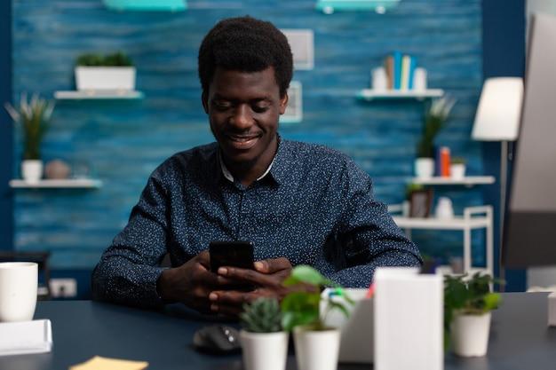Lachende tiener met smartphone chatten met vrienden tijdens vrije tijd zittend aan een bureau in de woonkamer. student bladert door zakelijke informatie op internet, leest universitaire sollicitatie-e-mail