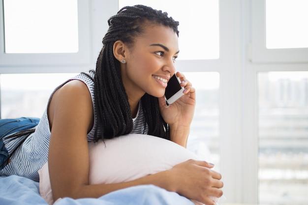 Lachende tiener praten over de telefoon liggen in bed