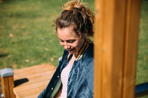Lachende tienerstudent die bij sportterrein rusten