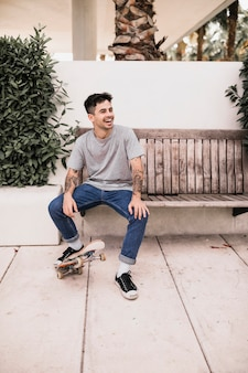 Lachende tienerzitting op houten bank door voet op skateboard te plaatsen
