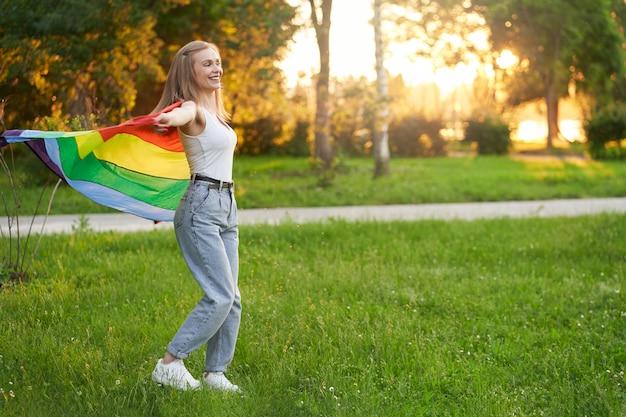 Lachende tolerante vrouw die danst met regenboog lgbt-vlag