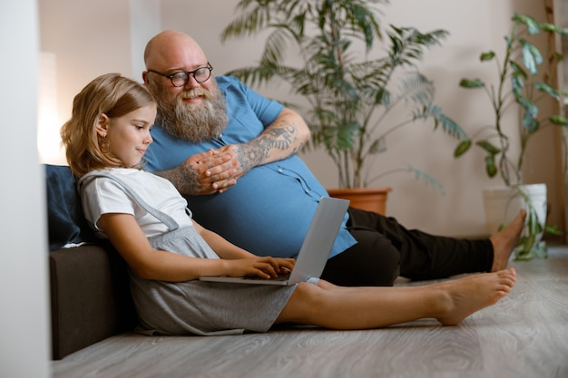 Lachende vader en schattig meisje kijken video via laptop zittend op de vloer in de slaapkamer