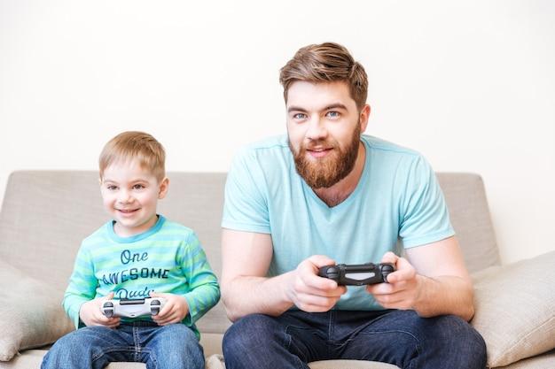 Lachende vader en zoon zitten en spelen computerspelletjes op de bank thuis