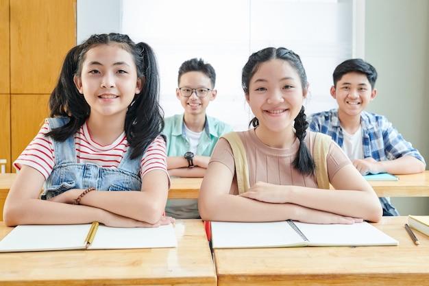 Lachende vietnamese scholieren zitten aan een bureau met geopende copybooks en glimlachen