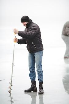 Lachende visser boort een gat in het ijs