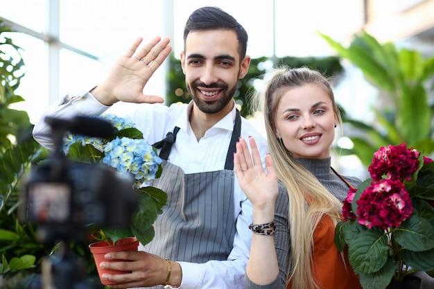 Lachende vlogger opname hortensia in bloempot. vrouw en man met bloeiende rode en blauwe hortensia zwaaien naar camcorder.