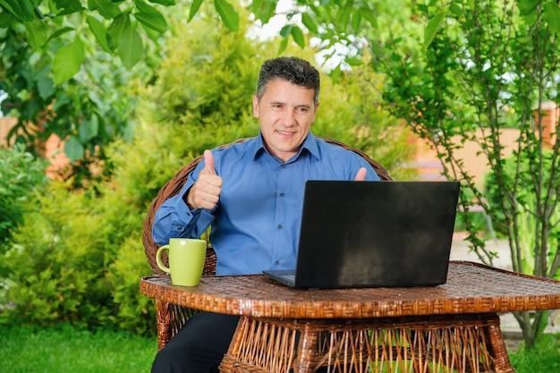Lachende volwassen blanke man koffie drinken en duimen opdagen met vingers naar zakenpartner via laptop in huis tuin. bedrijfsconcept op afstand