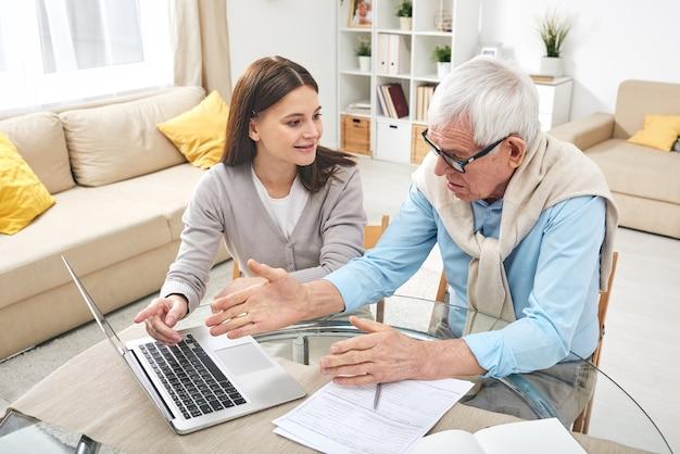 Lachende volwassen dochter zittend aan tafel met laptop en senior vader onderwijzen om online service te gebruiken