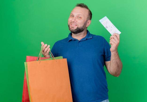 Lachende volwassen slavische man met boodschappentassen en vliegtuigticket geïsoleerd op groene muur