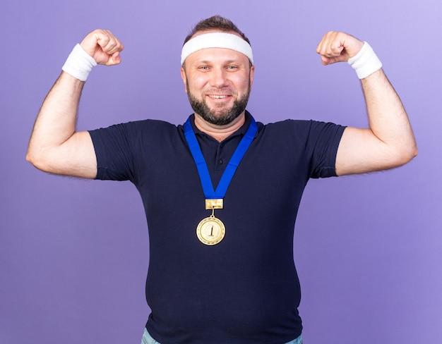 Lachende volwassen slavische sportieve man met gouden medaille om nek dragen hoofdband en polsbandjes spannende biceps geïsoleerd op paarse muur met kopie ruimte