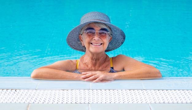 Lachende volwassen vrouw in buitenzwembad staande in de buurt van de rand met zonnebril en strohoed. zomer en vakantie concept