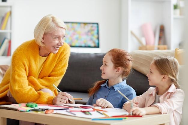 Lachende volwassen vrouw tekenen met twee kinderen