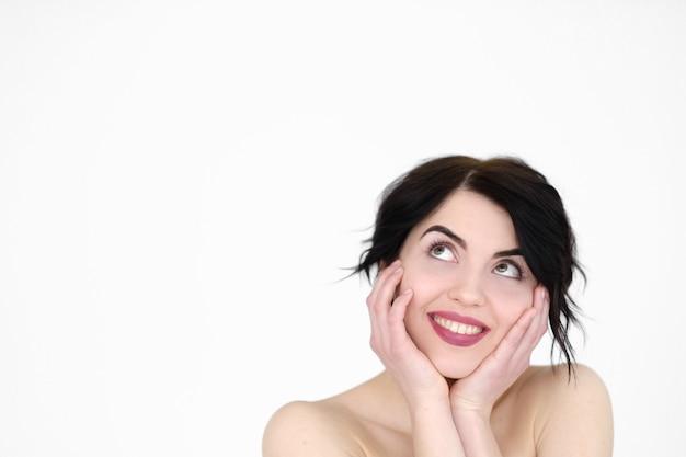 Lachende vreugdevolle vrouw met hoofd in handen op witte muur.