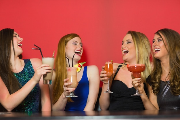 Lachende vrienden die cocktails houden