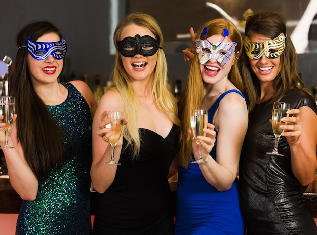 Lachende vrienden die maskers dragen die champagneglazen houden