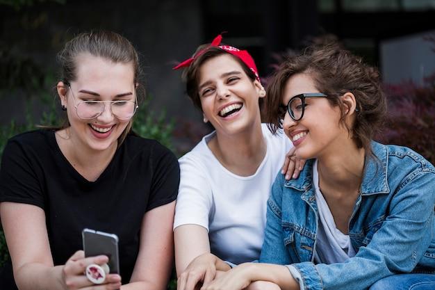 Lachende vrienden die smartphone in park bekijken