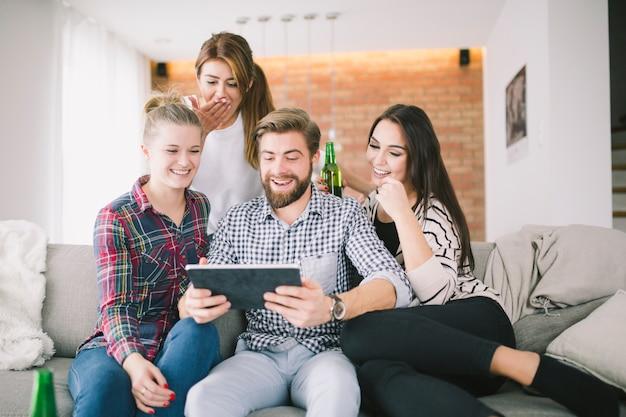 Lachende vrienden die tablet bekijken