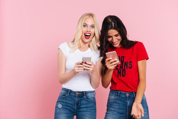 Lachende vrienden gebruikend smartphones en geïsoleerd glimlachen
