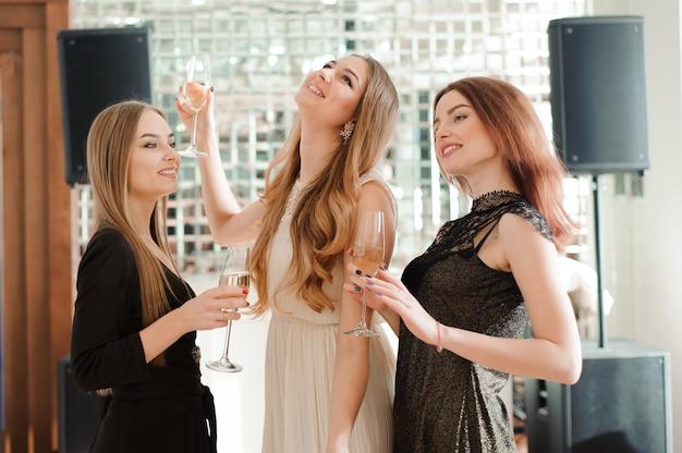 Lachende vrienden houden van glas champagne tijdens het dansen in de bar.