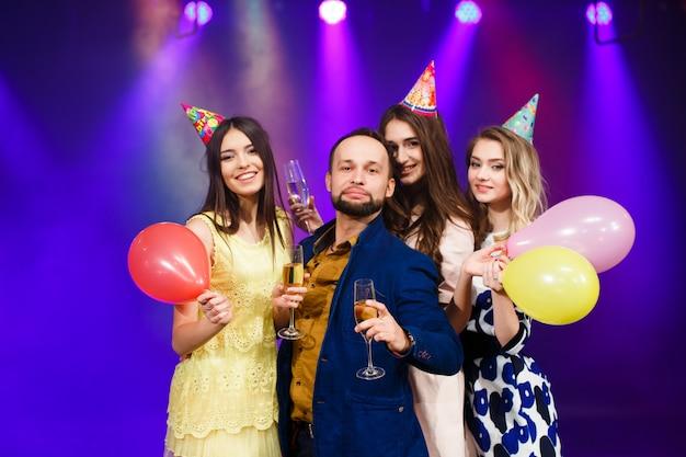 Lachende vrienden met glazen champagne in club