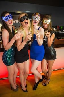 Lachende vrienden met maskers bij het houden van champagne