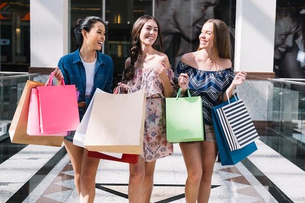 Lachende vrienden winkelen in winkelcentrum