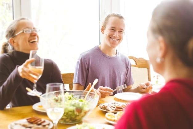 Lachende vrienden zitten aan de keukentafel. een vrolijke groep jonge mensen die samen plezier hebben.