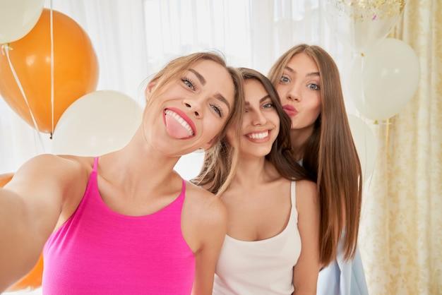 Lachende vriendinnen nemen selfie, gezichten maken.