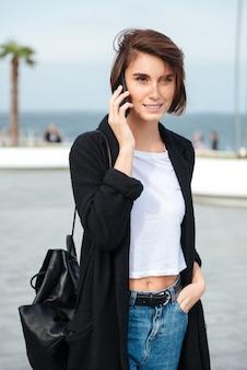 Lachende vrij jonge vrouw met rugzak lopend en pratend op mobiele telefoon buitenshuis