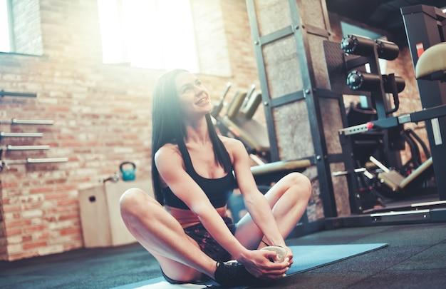 Lachende vrolijke brunette vrouw in sportkleding zittend op de mat in de sportschool
