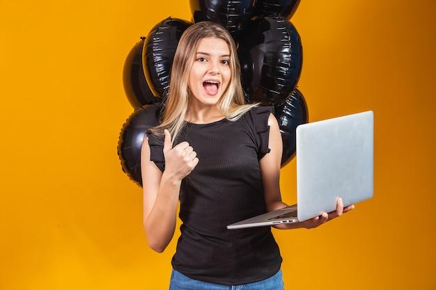 Lachende vrolijke grappige jonge brunette vrouw 20s met behulp van laptop pc-computer op heldere gele kleur achtergrond met lucht ballonnen studio portret. black friday-uitverkoop