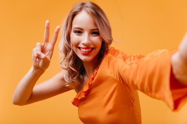 Lachende vrolijke vrouw in oranje jurk die foto van zichzelf