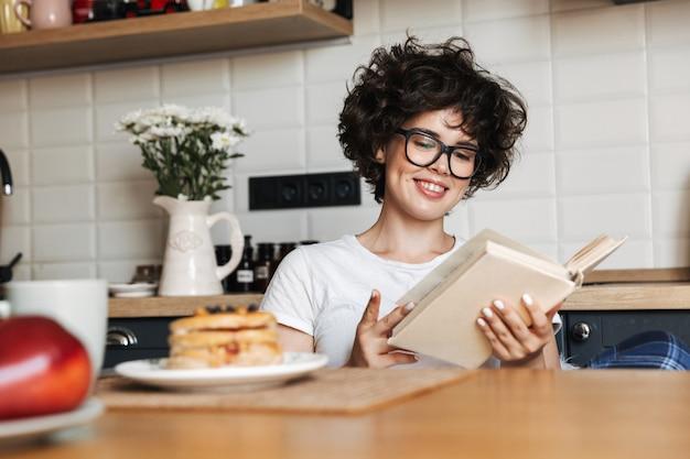 Lachende vrolijke vrouw lekker ontbijten zittend in de keuken thuis, een boek lezen