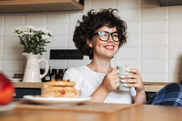 Lachende vrolijke vrouw lekker ontbijten zittend in de keuken thuis, koffie drinken