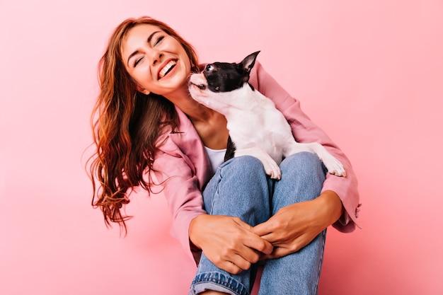 Lachende vrolijke vrouw zittend op de vloer met hond op haar knieën. indoor portret van aangename dame poseren met puppy op pastel.
