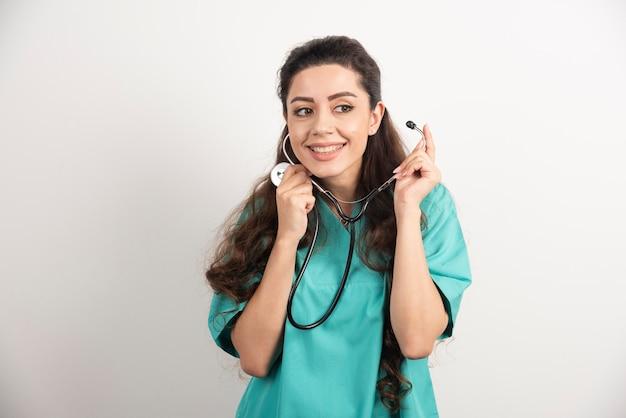 Lachende vrouw arts in uniform met stethoscoop.