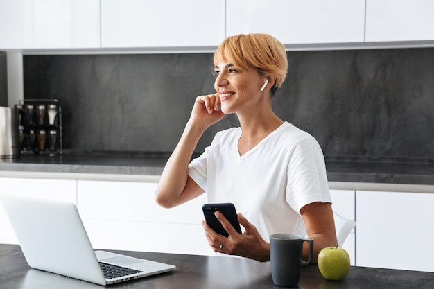 Lachende vrouw casualy gekleed met behulp van laptop computer zittend op een keuken, met oortelefoons