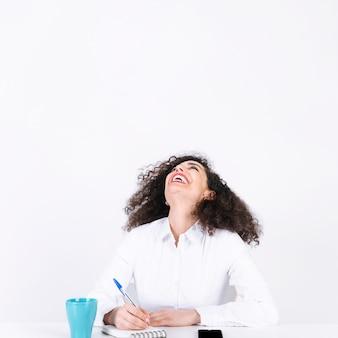 Lachende vrouw die aantekeningen maakt