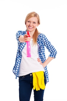 Lachende vrouw die de reiniger op je sproeit