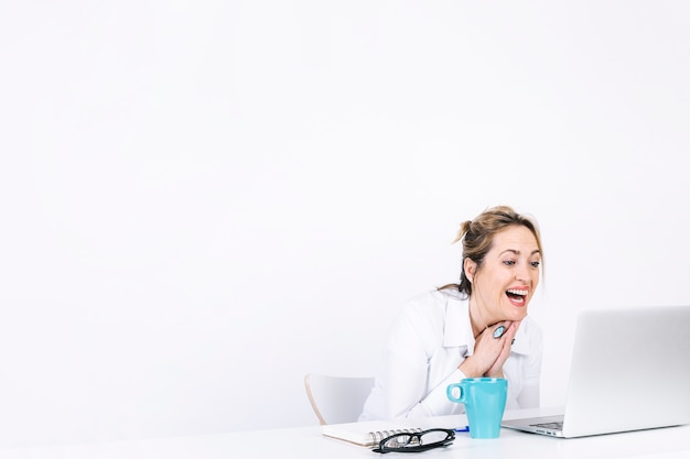 Lachende vrouw die laptop met behulp van