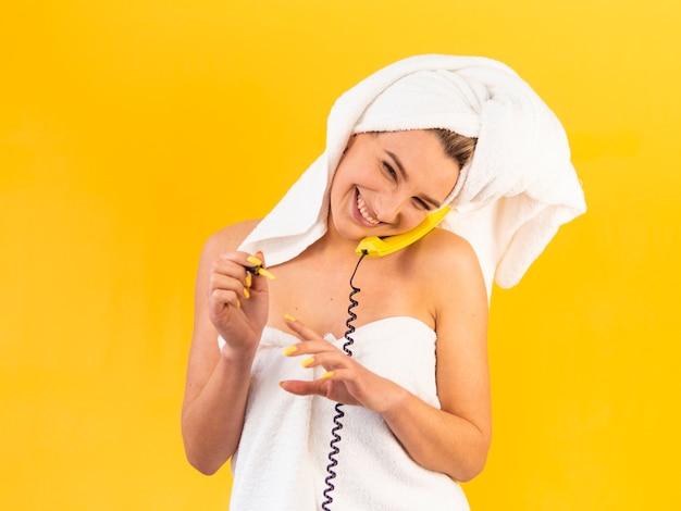 Lachende vrouw die op de telefoon spreekt